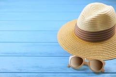 Vare los accesorios sombrero y gafas de sol en fondo de madera azul Fotografía de archivo
