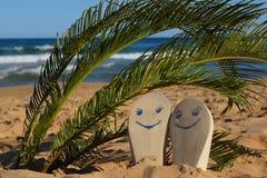 Vare los deslizadores con las caras felices pintadas debajo de hojas de palma en la arena cerca del mar Foto de archivo
