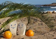 Vare los deslizadores con las caras felices pintadas y las naranjas debajo de hojas de palma en la arena cerca del mar Imagen de archivo