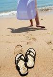 Vare los deslizadores en la arena, y los pies femeninos en un borde del mar Fotos de archivo libres de regalías