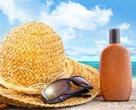 Vare los items y broncee la loción en la playa Imágenes de archivo libres de regalías
