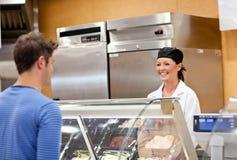 Varejista de sorriso do alimento com um cliente masculino Imagens de Stock Royalty Free