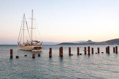 Varend bootjacht, de oceaan en de zonsondergang Bodrumhaven, Turkije Golfbrekers met staalposten Royalty-vrije Stock Foto's