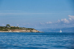 Varend jacht en eiland in het overzees Stock Fotografie