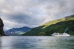 Varend schip op een fjord van Noorwegen met bergen erachter en regenboog en wolken hierboven royalty-vrije stock foto's