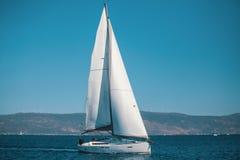 Varend schipjacht met witte zeilen in het Egeïsche Overzees stock afbeeldingen