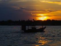 Varende boot in de rivier en de zonsondergang Stock Foto
