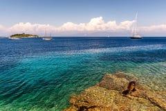 Varende boot en een klein eiland in het Ionische overzees royalty-vrije stock foto's