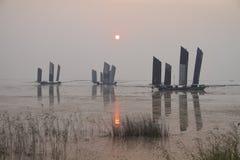 Varende boot in het meer bij zonsondergang royalty-vrije stock afbeelding