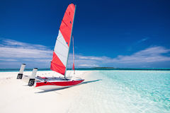 Varende boot met rood zeil op een strand van verlaten tropische islan Stock Afbeelding
