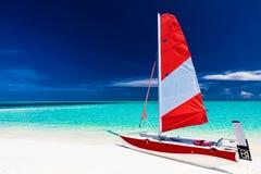 Varende boot met rood zeil op een strand van verlaten tropische islan Royalty-vrije Stock Foto's