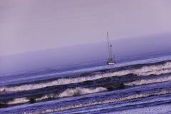Varende boot op de oceaan bij dageraad. royalty-vrije stock afbeelding
