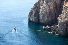 Varende boot rond de rotsen stock afbeelding