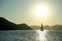 Varende boot tegen zonsondergang Stock Afbeeldingen
