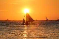 Varende boten bij het sundowning met een oranje hemel en een warm zonlicht Royalty-vrije Stock Fotografie