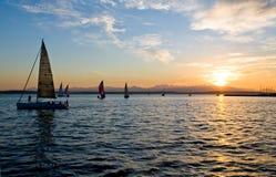 Varende boten bij zonsondergang stock afbeelding