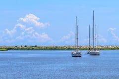 Varende boten die dichtbij strandkustlijn verankeren stock fotografie