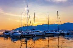 Varende boten in jachthaven bij zonsondergang. stock afbeelding