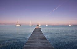 Varende boten voor een pijler met duidelijke hemel in Zuid-Korfu Griekenland Royalty-vrije Stock Foto