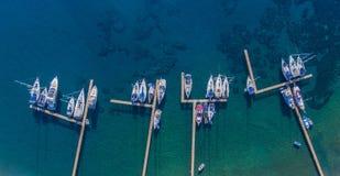 Varende die jachten en boten aan de houten pijlers worden vastgelegd stock foto's