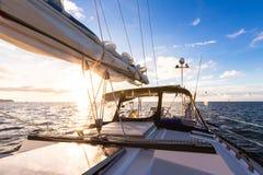 Varende jachtboot op oceaanwater tegen zonsondergang reis concept Royalty-vrije Stock Foto's