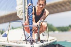 Varende mens die zich op dek en het voorbereiden van zeilboot voor de volgende reis bevinden stock foto