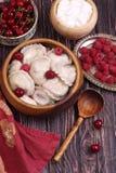 Vareniki用一棵樱桃和一个莓在一木碗submitt 免版税图库摄影