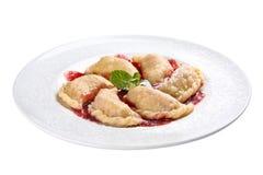 Vareniki con las cerezas Un plato ucraniano tradicional En un fondo blanco imagen de archivo