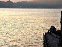 Varenna, Itália pares românticos do 30 de março de 2019 senta-se para contemplar o por do sol no lago Como imagens de stock