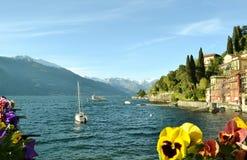 Varenna lakefront en de stad, sierbloemen, varende boot in een de lente zonnige dag stock afbeeldingen