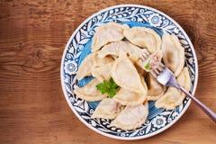 Varenyky, o vareniki, o pierogi, pyrohy ou as bolinhas de massa, enchidas com a carne e a cebola ou os cogumelos, podem ser servi Imagem de Stock