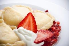 Varenyky with strawberry sauce Stock Photos