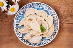 Varenyky, vareniki, pierogi, pyrohy или вареники, заполненные с мясом и луком или грибами, можно служить с сметаной стоковое фото