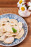 Varenyky, vareniki, pierogi, pyrohy or dumplings, filled with meat and onion or mushrooms, can be served with sour cream. Royalty Free Stock Image