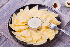 Varenyky, vareniki, pierogi, pyrohy or dumplings, filled with sweet cottage cheese farmer cheese and served with sour cream Royalty Free Stock Photography
