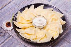 Varenyky, vareniki, pierogi, pyrohy o gnocchi, riempiti di formaggio dolce dell'agricoltore della ricotta e serviti con panna aci Immagini Stock Libere da Diritti