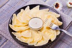Varenyky, vareniki, pierogi, pyrohy o gnocchi, riempiti di formaggio dolce dell'agricoltore della ricotta e serviti con panna aci Immagine Stock