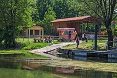 A lively lakeside bar with some people on a summer afternoon. VARESE, ITALY - MAY 08, 2011: A lively lakeside bar with some people on a summer afternoon royalty free stock photo