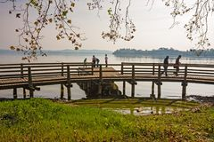 Some people are walking on the wooden boardwalk by the lake. VARESE, ITALY - OCTOBER 07, 2012: Some people are walking on the wooden boardwalk by the lake Stock Photos