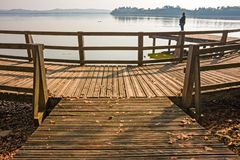 Some people are walking on the wooden boardwalk by the lake. VARESE, ITALY - OCTOBER 07, 2012: Some people are walking on the wooden boardwalk by the lake Stock Images