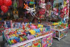 Variété énorme de jouets colorés étant vendus à une stalle de bord de la route Image libre de droits