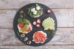 Variété de canape avec des saumons, avocat, mozzarella, tomate, pesto, olives, fromage fondu Mélange de différents casse-croûte e Photos libres de droits