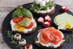Variété de canape avec des saumons, avocat, mozzarella, tomate, pesto, olives, fromage fondu Mélange de différents casse-croûte e Photos stock