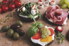 Variété de canape avec des saumons, prosciutto, avocat, mozzarella, tomate, pesto, olives, fromage fondu Mélange des casse-croûte Photos libres de droits