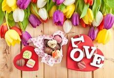 Variété de chocolats dans la boîte en forme de coeur Images stock