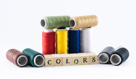 Variété de fils colorés placés l'un à côté de l'autre et de cubes en bois formant les couleurs de mot Photos libres de droits