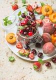 Variété de fruits saine d'été Merises dans le pot en verre, les fraises, les pêches, les abricots et des feuilles en bon état sur photos libres de droits