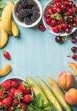 Variété de fruits saine d'été Merises, fraises, mûres, pêches, bananes, tranches de melon et feuilles en bon état Photo libre de droits