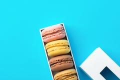 Variété de macarons roses de moka de jaune de café de chocolat de différentes saveurs multicolores dans le boîte-cadeau blanc ave photos stock