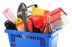 Variété de produits de consommation dans le panier à provisions en plastique d'isolement photographie stock libre de droits